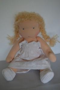 zittende pop in witte jurk