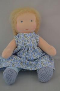 ledematenpopje blauw jurkje zittend
