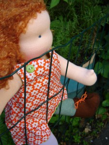 waldorf doll climbing the fence